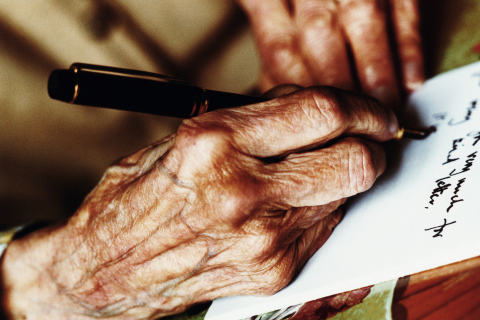 Elderly woman writing letter with fountain pen, close-up of hands